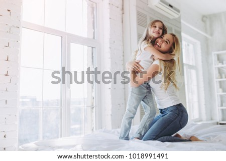 Attractive young woman and her little cute daughter are having fun in bed while being at home together. Happy Mother's Day! #1018991491