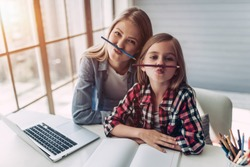 Attractive young woman and her little cute daughter are sitting at the table and having fun while doing homework together. Mother helps daughter with her school classes.