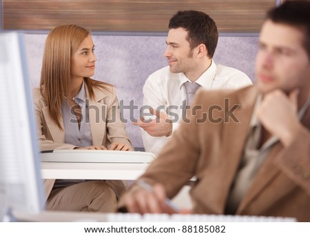 Attractive young woman and man chatting at computer course.?