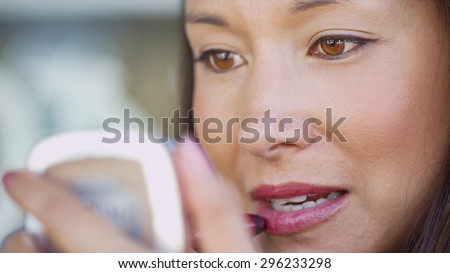 Attractive young woman applying lipstick using a portable vanity mirror