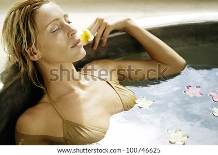 Attractive young woman bathing in a bath of flowers in a health spa.
