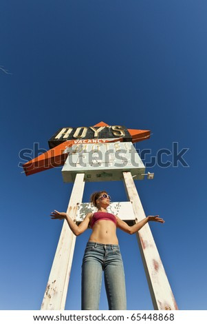 Attractive, young woman being silly at an abandoned roadside motel sign.