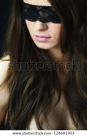 Attractive young woman blindfolded. Looking over her shoulder