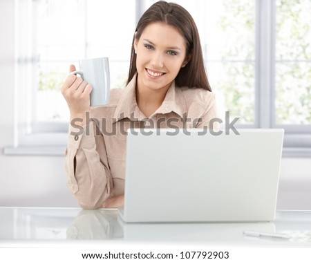 Attractive young woman browsing internet at home, using laptop, drinking tea, smiling.
