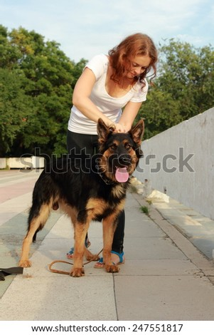 Attractive young woman brushing her dog German shepherd breed outdoor