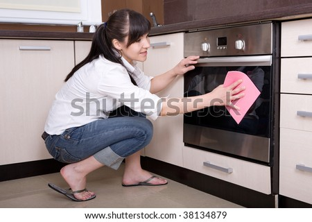 attractive young woman cleaning kitchen