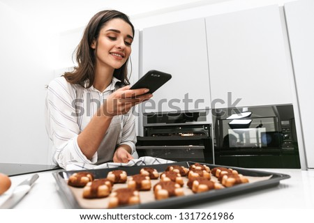 Attractive young woman cooking tasty cookies on a tray while standing at the kitchen, taking a picture