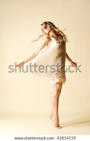 attractive young woman dancing, studio light background