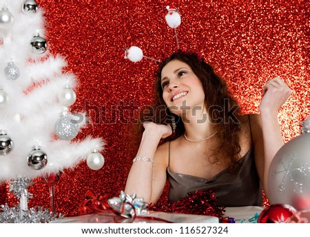 Attractive young woman decorating a white Christmas tree while sitting at a table full of ornaments in front of a red glitter background, smiling.