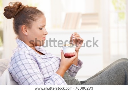 Attractive young woman dieting, eating yoghurt in bed.?