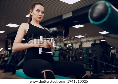 Attractive young woman doing exercises for the muscles of the arms and back in a gym Stock foto ©