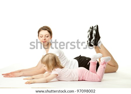 Attractive young woman doing sport exercises with her little daughter on white background