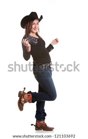 Attractive young woman dressed in a cowboy hat and boots with spurs, dancing.  Isolated on white.