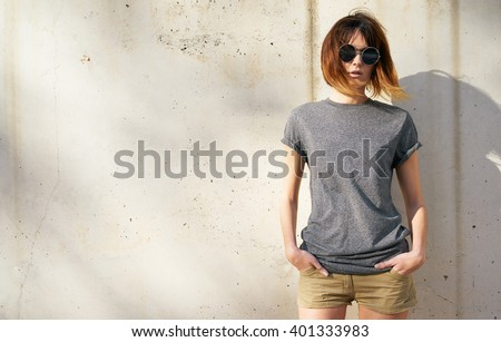 attractive young woman dressed in a gray blank t-shirt posing on a background of a concrete wall in the rays of the setting sun