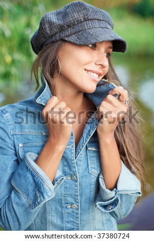 Attractive young woman dressed in jean and beret holding on herself jacket collar