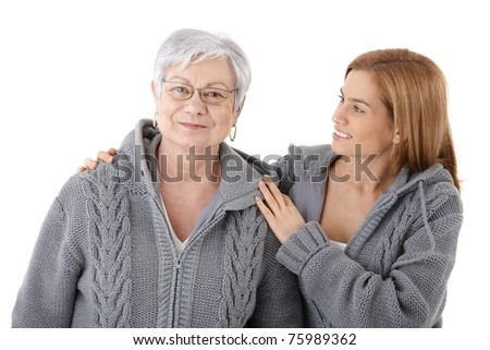 Attractive young woman embracing senior mother with love, smiling, wearing identical cardigans.? - stock photo