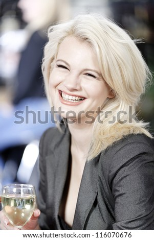 Attractive young woman enjoying a glass of white wine in a wine bar.