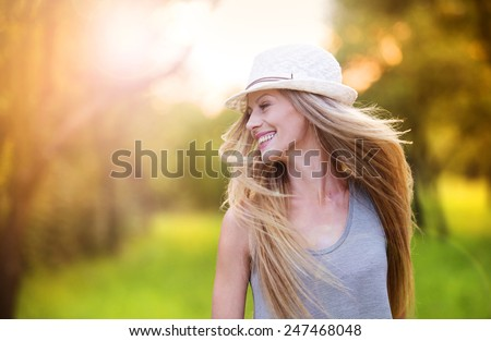 Attractive young woman enjoying her time outside in park with sunset in background. #247468048