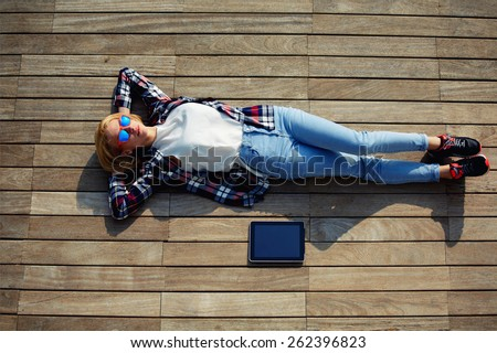 Attractive young woman enjoying sunshine while lying on the wooden pier with her tablet computer, female carefree freelancer girl resting after work outside, young female lying relaxed on a jetty