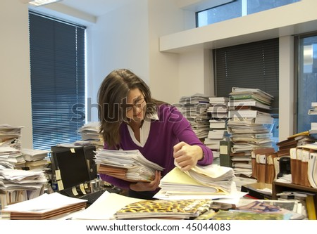 Attractive young woman executive at work in a very messy office