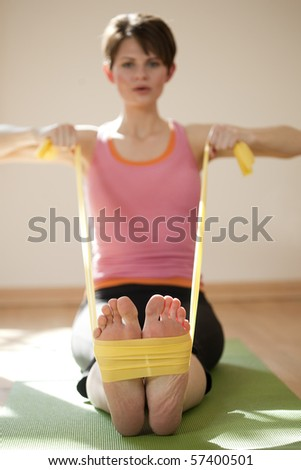 Attractive young woman exercises with resistance bands around her feet. Vertical shot.