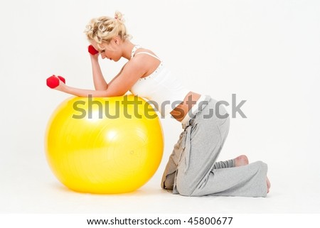 Attractive young woman exercising with dumbbells on a big fitness ball