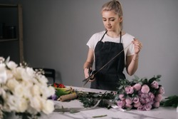 Attractive young woman florist wearing apron cutting rope for wrapping bouquet of flowers at the table on white background. Concept of working with flowers, floral business.
