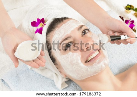 Attractive young woman getting a facial mask in the beauty spa