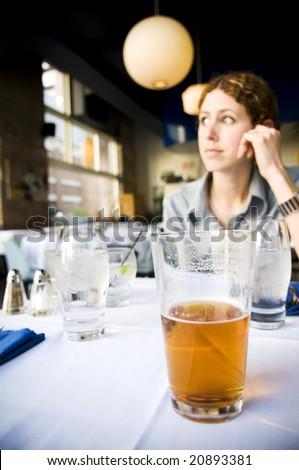 Attractive young woman having drinks(focus on beer)