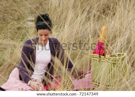 attractive young woman having picnic outside