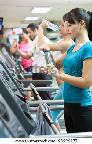 attractive young woman holding a bottle of water at the gym, needed refreshment