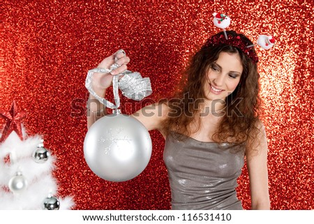 Attractive young woman holding an over sized Christmas bar ball against a red glitter background, smiling.