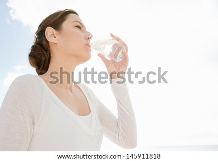 Attractive young woman holding and drinking from a glass of clean water against a sunny sky hydrating and feeling healthy