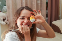 Attractive Young Woman Holding Easter Egg and paint brush in hands. She smiles and happy to spend time at home and preparing for Easter Holliday.