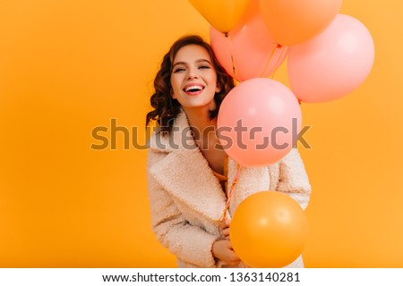 Attractive young woman holding pink balloons and smiling. Studio shot of blissful birthday girl isolated on yellow background. #1363140281