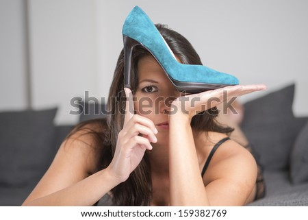 Attractive young woman holding up an elegant high heeled turquoise ladies court shoe in a plush finish, beauty and fashion concept