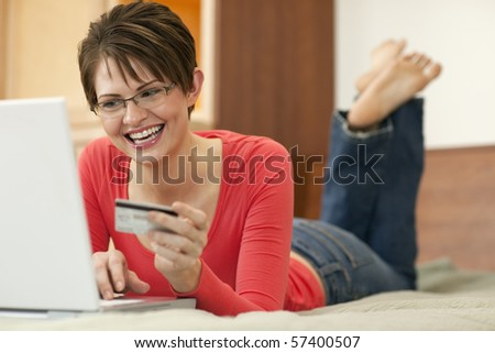 Attractive young woman holds up the credit card she is using to shop with on her laptop computer. Horizontal shot.