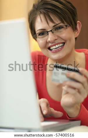 Attractive young woman holds up the credit card she is using to shop with on her laptop computer. Vertical shot.