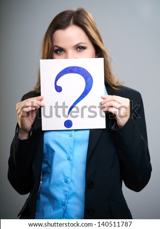 Attractive young woman in a black jacket. Woman holds a poster with a big question mark. Poster covers her face. On a gray background