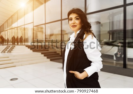 attractive young woman in a black suit posing, walking around the city of Baku