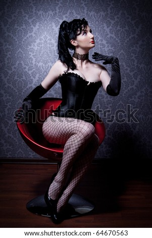 Attractive young woman in a corset is sitting on a chair and looks into the camera