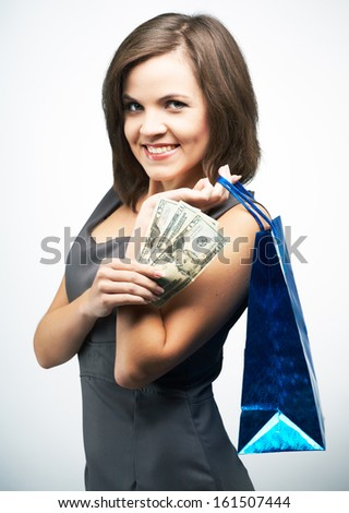 Attractive young woman in a gray business dress. Holds a gift bag and money. On a gray background