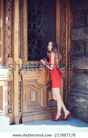 Attractive young woman in a open back red dress and heels in front of the old antique wooden door looking inside, on the European city street