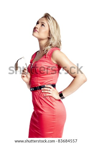 Attractive young woman in a red dress with sun glasses in her hand, looking up. - stock photo