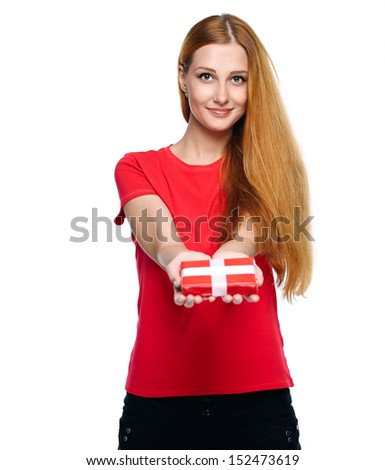 Attractive young woman in a red shirt with long red hair. Holds a red gift box. Isolated on white background