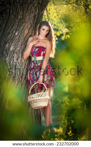 Attractive young woman in a summer fashion shot. Beautiful fashionable young girl with straw basket in park near a tree. Brunette woman posing in forest in a sunny day, outdoor shot