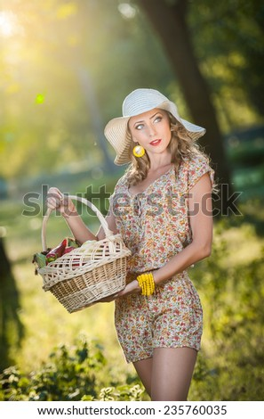 Attractive young woman in a summer fashion shot. Beautiful fashionable young girl with straw basket and hat in park near a tree in sunshine. Blonde woman posing in forest in a sunny day, outdoor shot