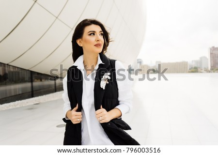 attractive young woman in a white shirt walking around the city of Baku in Azerbaijan
