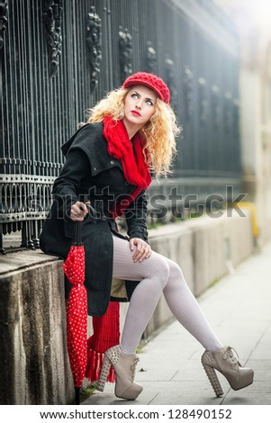 attractive young woman in a winter fashion shot.Beautiful fashionable young girl with red umbrella in the street