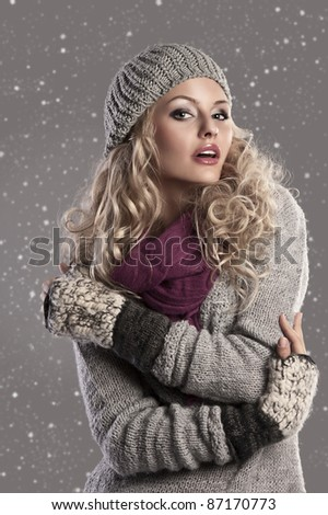 attractive young woman in a winter fashion shot wearing a wool cap, a grey woolen sweater and a purple scarf